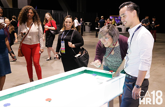 CAHR18 attendees mingling & playing air hockey